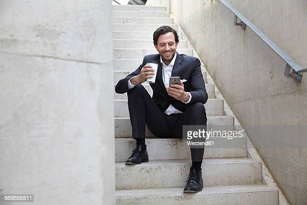 Businessman with coffee to go using smartphone in a modern building