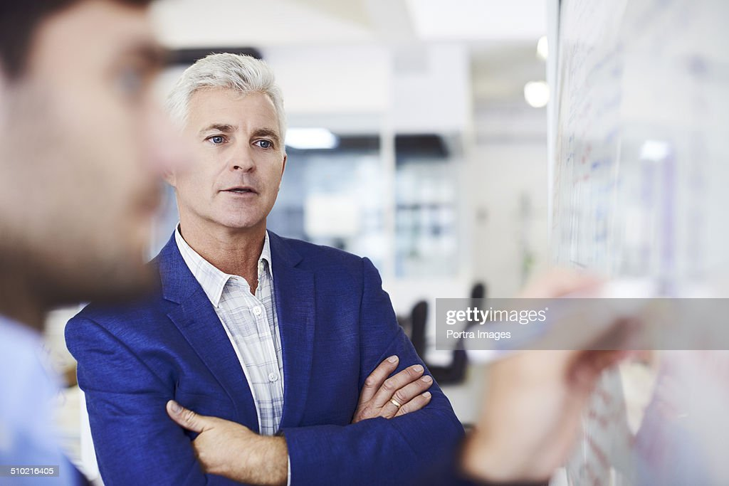 Businessman with colleague writing on whiteboard : Stock Photo