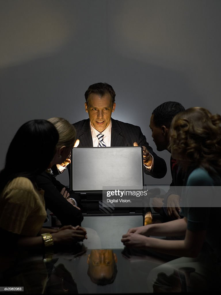Businessman With Colleagues Sitting in a Dark Office Opening a Bright Briefcase : Stock Photo