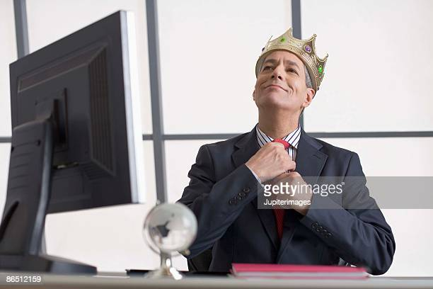 businessman with crown sitting at desk - arrogance stock pictures, royalty-free photos & images