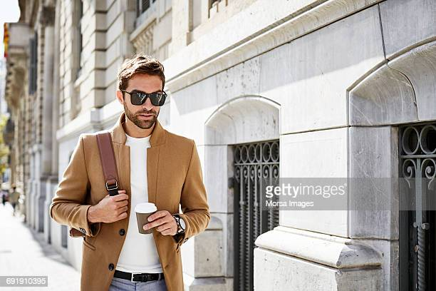businessman with cup and bag walking on sidewalk - brown jacket stock pictures, royalty-free photos & images