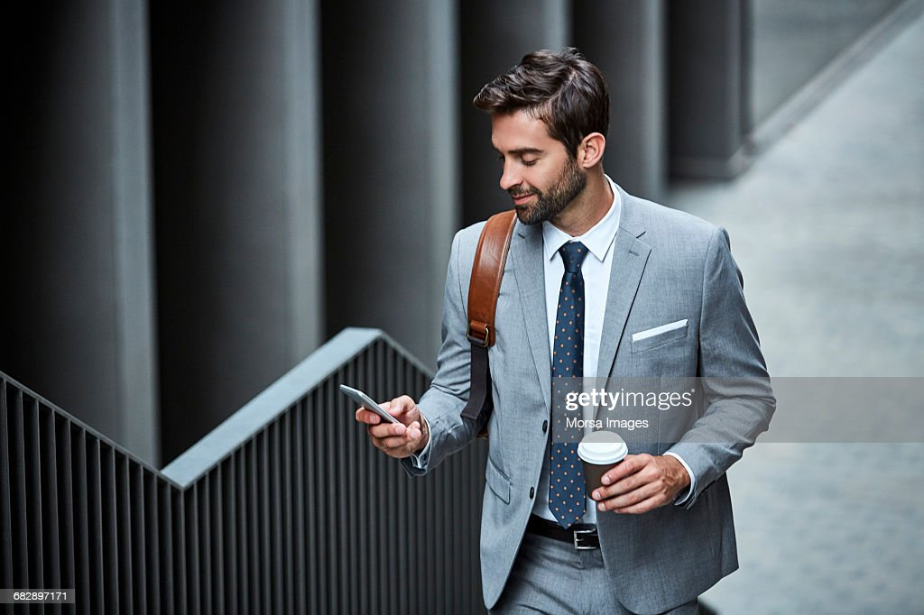 Businessman with cup and mobile phone on stairs : Stock Photo
