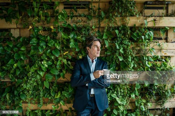 businessman with cup of coffee in green office - green suit stock pictures, royalty-free photos & images