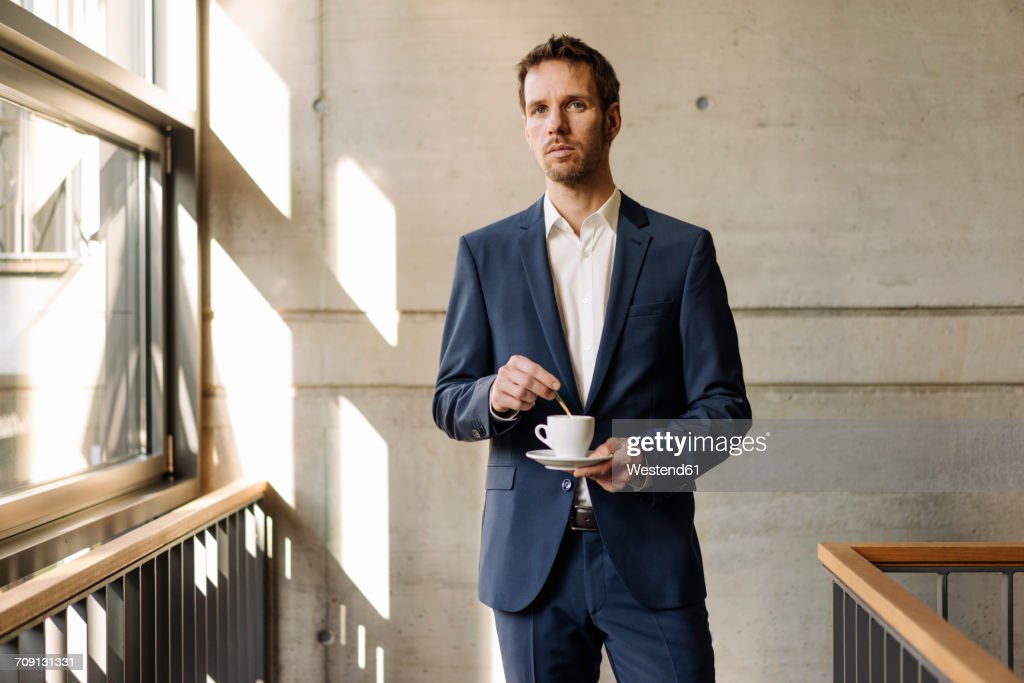Businessman with cup of coffee in staircase : Stock-Foto