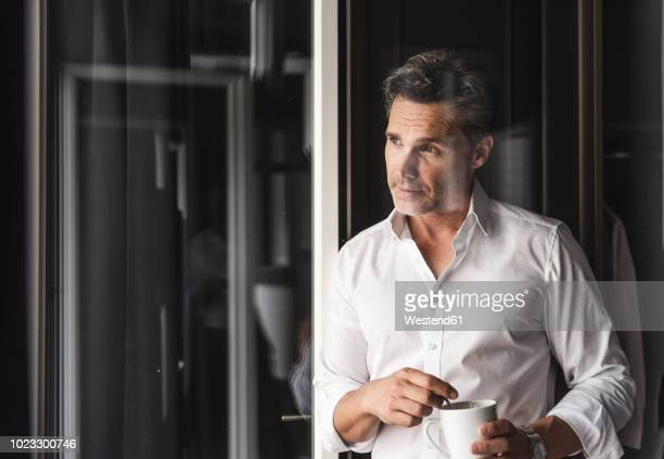 businessman with cup of coffee looking out of window at home - morgen stock-fotos und bilder