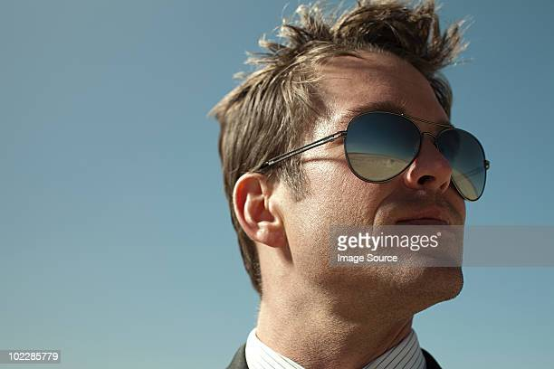 Businessman with desert reflected in sunglasses