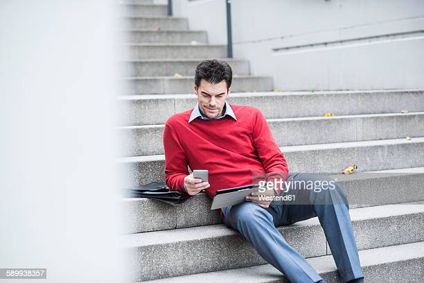 Businessman with digital tablet and smartphone sitting on stairs
