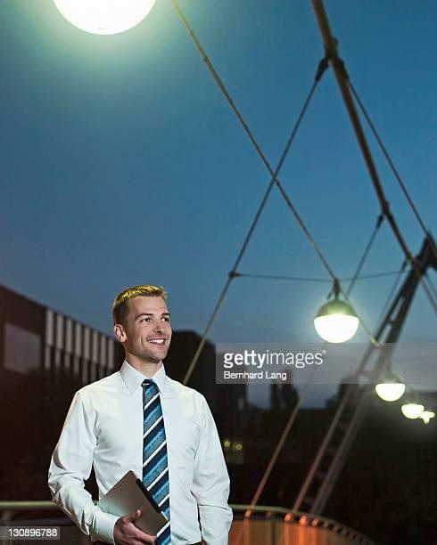 Businessman with digital tablet at dusk