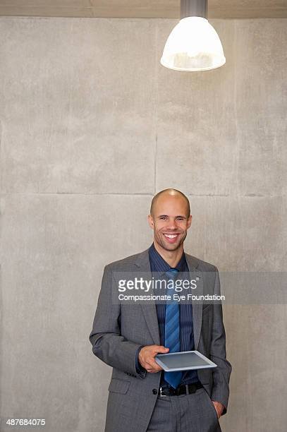 Businessman with digital tablet in office hallway