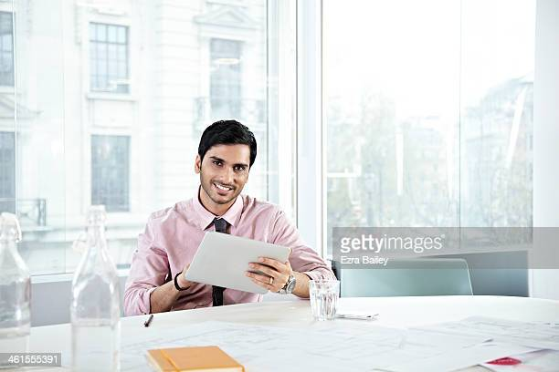 Businessman with digital tablet in white office.