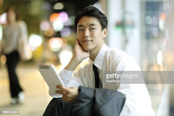 businessman with digital tablet sitting on outdoors - korean ethnicity stock pictures, royalty-free photos & images