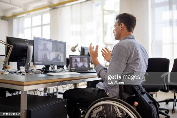 businessman with disability having a video call at his desk - disability stock pictures, royalty-free photos & images