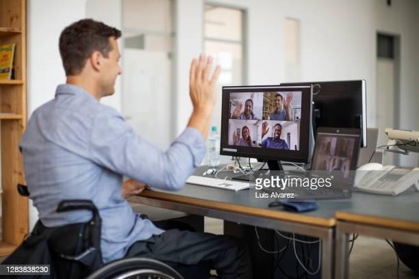 businessman with disability having video call with team - envolvimento dos funcionários imagens e fotografias de stock