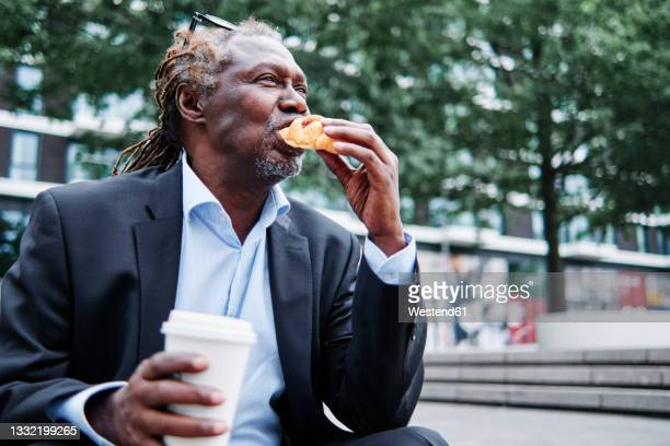 businessman with disposable cup eating croissant - on the move stock pictures, royalty-free photos & images