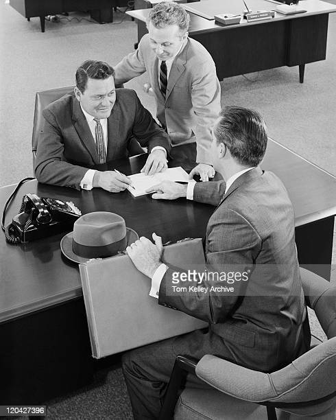Businessman with document on table, smiling
