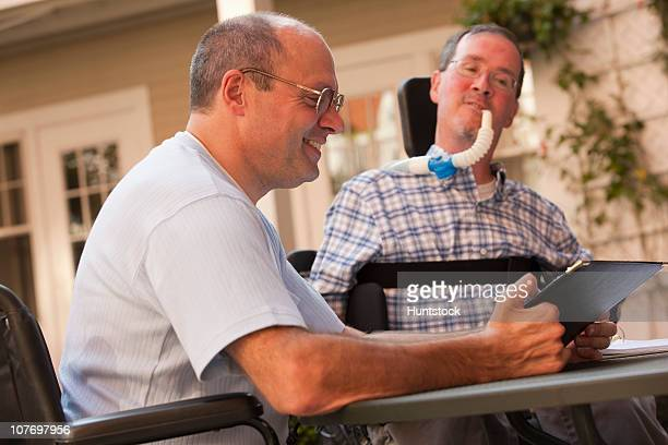 businessman with duchenne muscular dystrophy and a man with friedreich's ataxia working at a cafe - duchenne muscular dystrophy stock photos and pictures