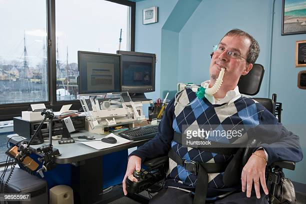 businessman with duchenne muscular dystrophy using a breathing ventilator in an office - duchenne muscular dystrophy stock photos and pictures