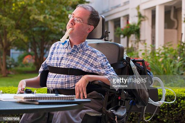 businessman with duchenne muscular dystrophy using breathing ventilator and doing paperwork at a cafe - duchenne muscular dystrophy stock photos and pictures