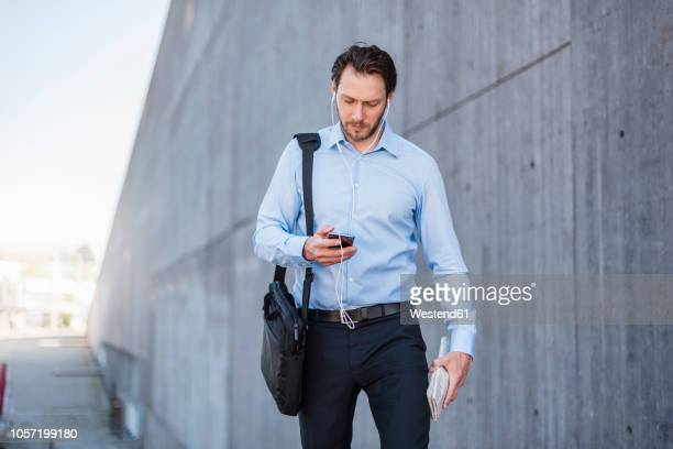 Businessman with earbuds walking along concrete wall looking at smartphone