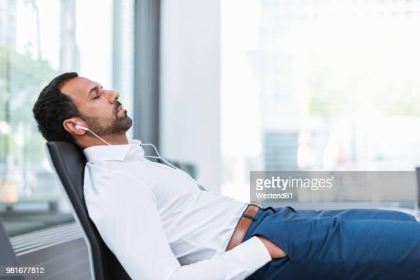 Businessman with earphones, closed eyes