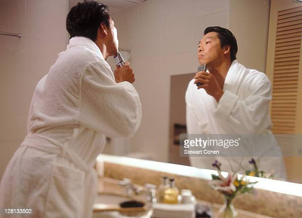 Businessman with electric razor in hotel