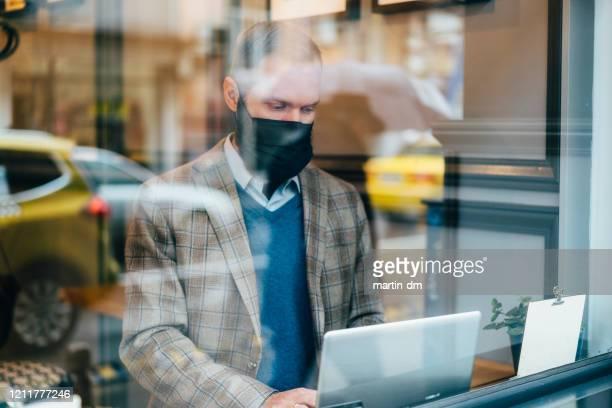 geschäftsmann mit gesichtsmaske - atemschutzmaske stock-fotos und bilder