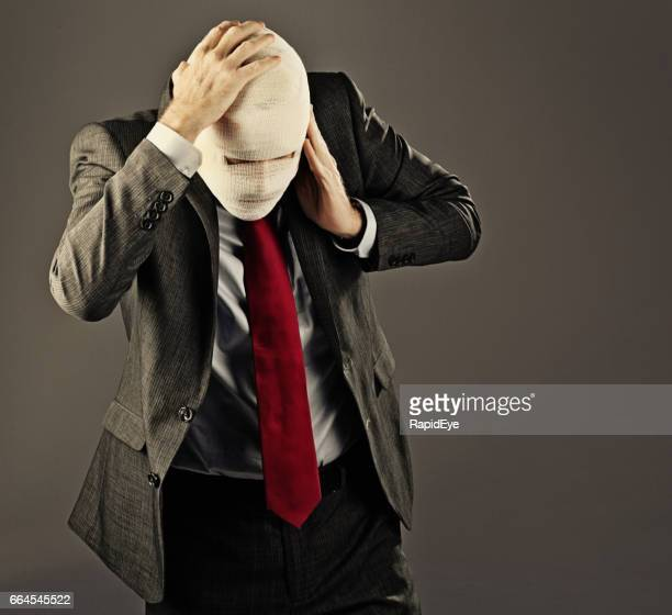 Businessman with face obscured by bandages clutches painful head
