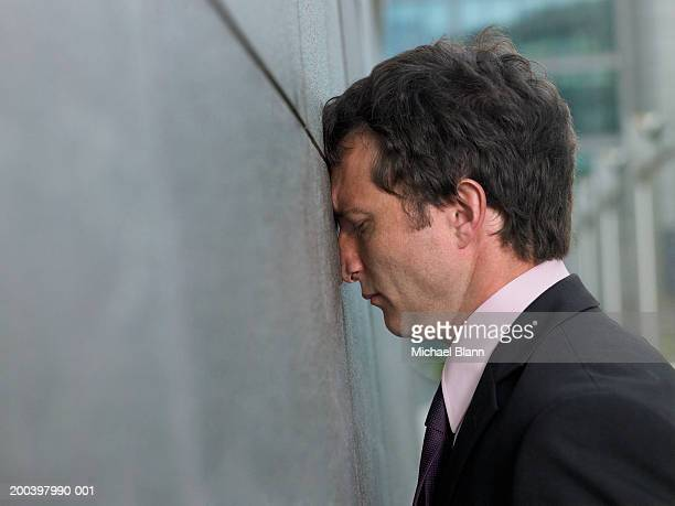 businessman with face pressed against wall, profile, close-up - aborto fotografías e imágenes de stock
