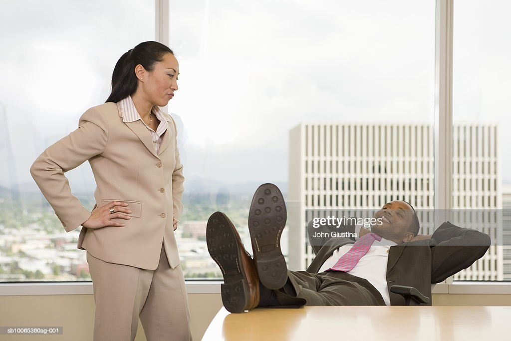 Businessman with feet on desk, businesswoman watching : Foto stock