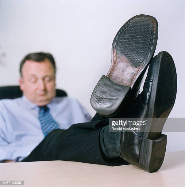 businessman with feet on desk - mens dress shoes stock pictures, royalty-free photos & images