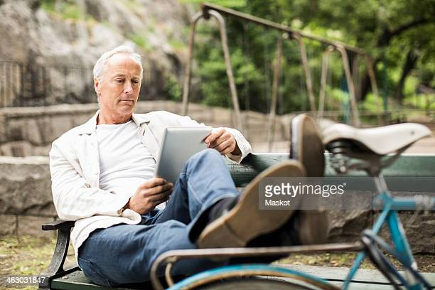 Businessman with feet up on bicycle using digital tablet on park bench