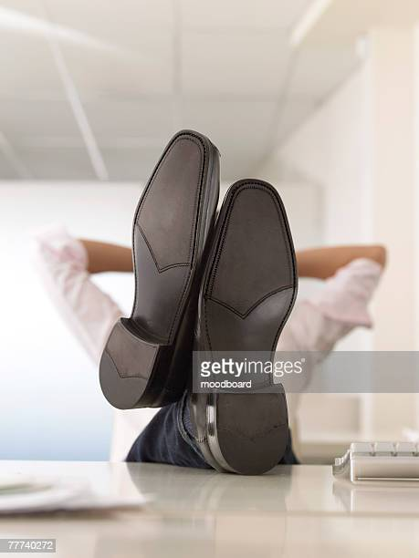 businessman with feet up on desk - nette schoen stockfoto's en -beelden
