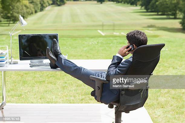 Businessman with feet up sitting at desk in field talking on cell phone
