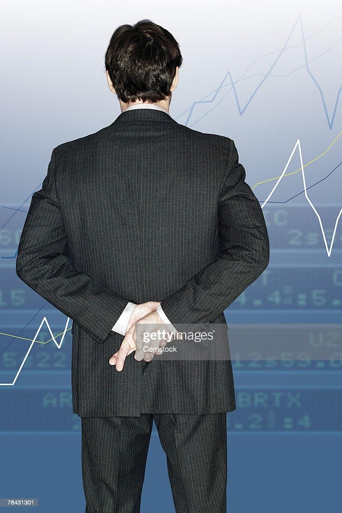 Businessman with fingers crossed behind back facing stock market graph : Stock Photo
