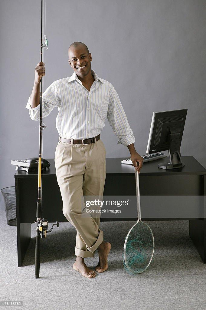 Businessman with fishing pole : Stockfoto