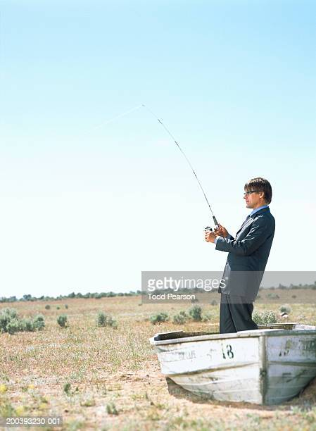 Businessman with fishing pole, standing in boat in desert