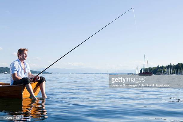 businessman with fishing rod in rowboat - angeln stock-fotos und bilder