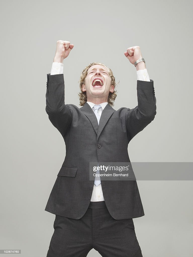 businessman with fists in the air celebrating : Stockfoto