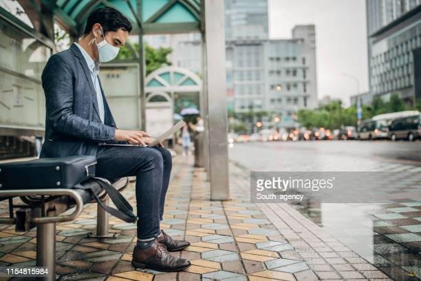 businessman with flu mask using laptop on bus station - masks stock pictures, royalty-free photos & images