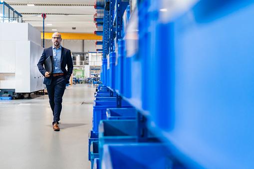 Businessman with folder walking in factory - gettyimageskorea