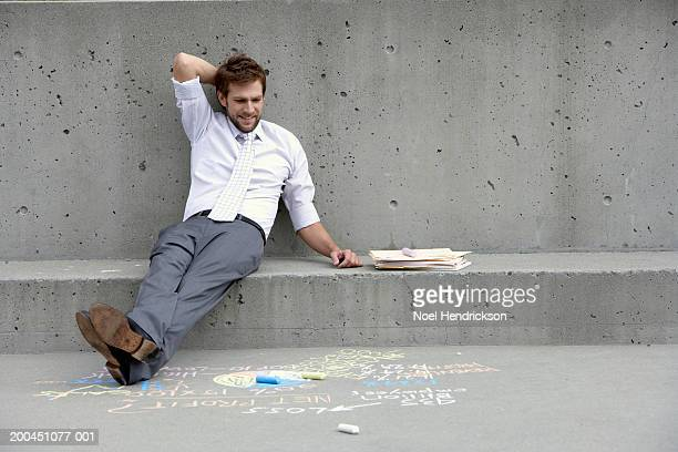 Businessman with folders, and looking at writing on sidewalk
