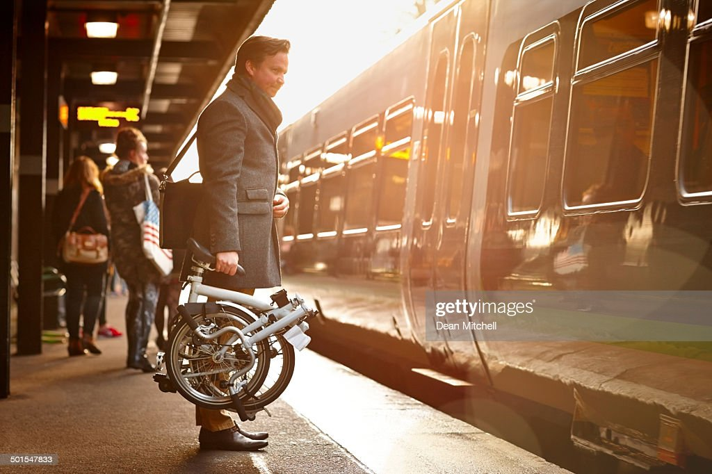 Businessman with folding cycle boarding train : Stock Photo