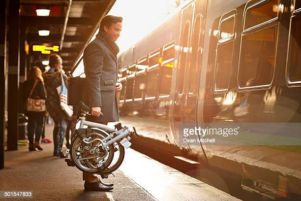 businessman with folding cycle boarding train - fietsen stockfoto's en -beelden