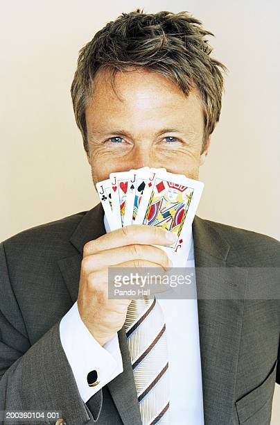 businessman with four knaves playing cards in front of mouth, portrait - poker stock-fotos und bilder