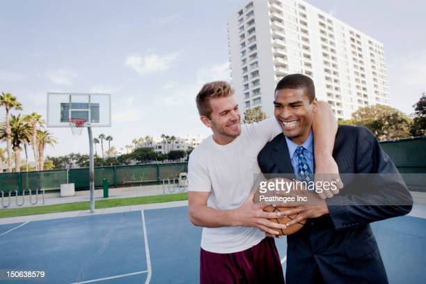 Businessman with friend on basketball court