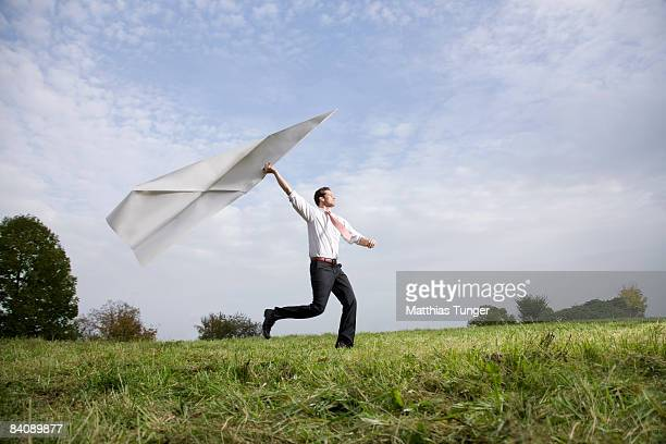 Businessman with giant paper aeroplane