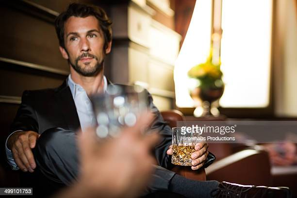 Businessman with glass of whiskey in a bar