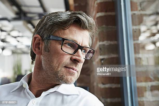 Businessman with glasses looking out of window