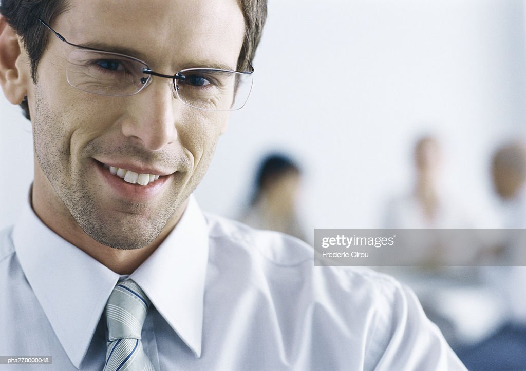 Businessman with glasses, smiling at camera : Stockfoto