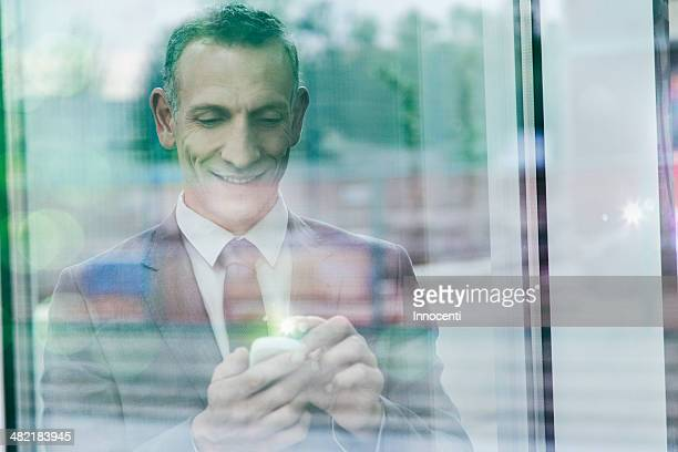 Businessman with glowing finger using smartphone touchscreen